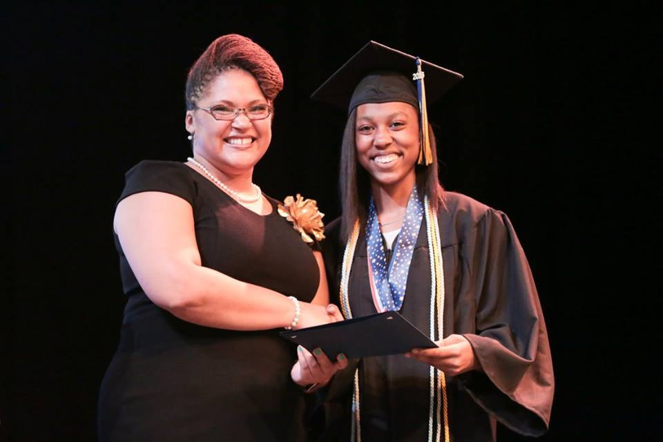 CEO Charleita Richardson smiling with a graduating student.