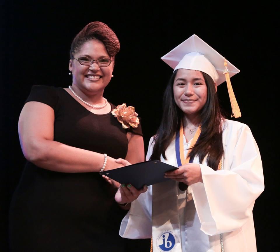 CEO Charleita Richardson smiling with a graduating student.